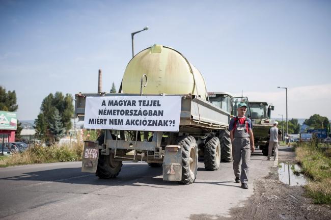Pécs, 2014. július 8. Transzparens egy traktor utánfutóján a Mecsek Füszért logisztikai bázisa előtt Pécsett a tejtermelők demonstrációján 2014. július 8-án. A termelők a tiltakozással a fogyasztók figyelmét szeretnék felhívni arra, hogy részesítsék előnyben a magyar tejtermékeket az importtal szemben, valamint figyelmeztetni akarnak egyes, szerintük aránytalanul nagy mennyiségben import tejtermékeket forgalmazó kereskedőket arra, hogy preferálják a magyar tejtermékeket. MTI Fotó: Sóki Tamás