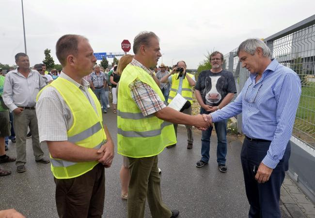 Nagytarcsa, 2014. július 8. Istvánfalvi Miklós a demonstrációs bizottság tagja petíciót ad át Foltin Ottónak, a Foltin Globe Kft. ügyvezető igazgatójának (j) a tejtermelők demonstrációján a társaság nagytarcsai logisztikai központjánál 2014. július 8-án. A termelők a tiltakozással a fogyasztók figyelmét szeretnék felhívni arra, hogy részesítsék előnyben a magyar tejtermékeket az importtal szemben, valamint figyelmeztetni akarnak egyes, szerintük aránytalanul nagy mennyiségben import tejtermékeket forgalmazó kereskedőket arra, hogy preferálják a magyar tejtermékeket. MTI Fotó: Máthé Zoltán
